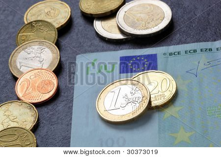 Coins and a banknote on black background