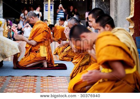 CHIANG MAI, THAILAND - FEBRUARY 4: Buddhist monks praying on evening religion ceremony in Doi Suthep Wat on February 4, 2012 in Chiang Mai, Thailand
