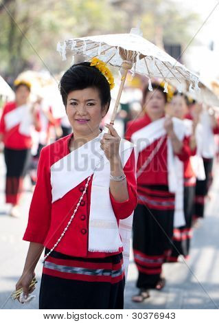 CHIANG MAI, THAILAND - FEBRUARY 4: Traditionally dressed womans in procession on Chiang Mai 36th Flower Festival on February 4, 2012 in Chiang Mai, Thailand