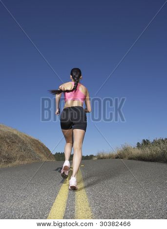 Woman running in the middle of the road