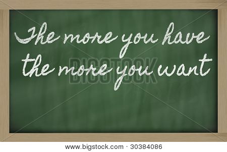Expression -  The More You Have, The More You Want - Written On A School Blackboard With Chalk