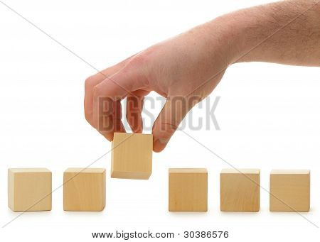The Hand Establishes A Wooden Cube In Row