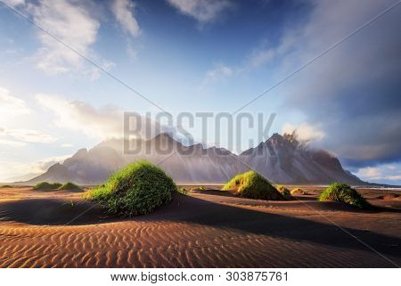poster of Gorgeous landscape with black sand desert dunes and grassy bumps near famous Stokksnes mountains on