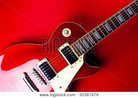 Deep red metallic vintage solid body electric guitar on deep red background.