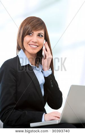 Portrait Of Businesswoman With Laptop And Cell Phone