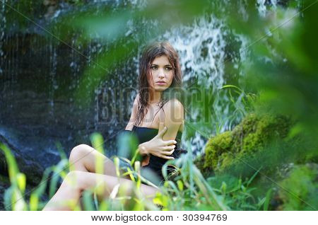 Young and beautiful girl in bikini taking bath in a waterfall