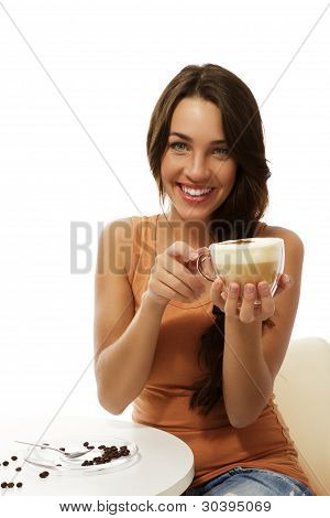 happy young woman with a cappuccino coffee sitting at a table