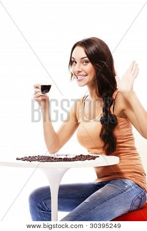 happy young woman sitting at a table holding cup of espresso coffee