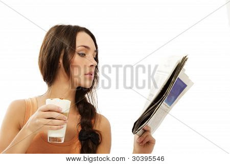 young woman reading newspaper holding latte macchiato coffee