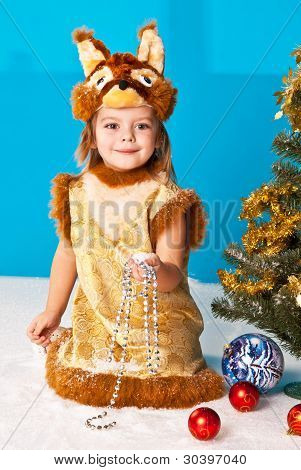 Little girl in Fox (Squirrel) suit near New Year tree at blue background and white snow on floor
