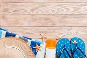 Flip Flops, Straw Hat, Starfish, Sunscreen Bottle, Body Lotion Spray On Wooden Background Top View . poster