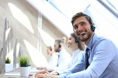 Portrait Of Call Center Worker Accompanied By His Team. Smiling Customer Support Operator At Work. poster