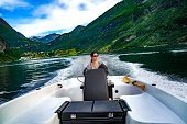 Woman driving a motor boat. Geiranger fjord, Beautiful Nature Norway.Summer vacation. Geiranger Fjor poster