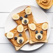 Funny Bear Face Sandwiches With Peanut Butter, Banana And Blueberries Served On Plate On Wooden Back poster