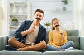Funny family! Father and his child daughter with a paper accessories. Funny girl holding moustache o poster