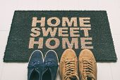 Door mat Shoes at front entrance of condo apartment. Written welcome sign Home Sweet Home welcoming  poster