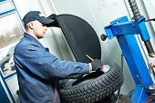 stock photo of lubricant  - serviceman repairman worker lubricating car tyre at workshop befor fitting - JPG
