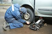 mechanic repairman making tyre fitting by using jack for car lifting