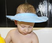 Visor From Water For Washing The Head. Little Happy Boy In The Bathroom Washes His Head. On His Head poster
