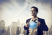 stock photo of nerd  - Young businessman showing the superhero suit under his shirt with cityscape in the background - JPG