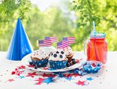 celebration, patriotism and holidays concept - glazed cupcakes with american flags, juice glass or m poster