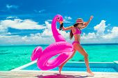 Vacation fun woman in bikini with funny inflatable pink flamingo pool float running of joy jumping b poster