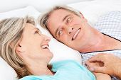 Happy smiling senior couple cuddling in bed