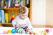 Adorable Baby Girl Playing With Educational Toys In Nursery. Happy Healthy Child Having Fun With Col poster