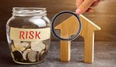 Jar With Coins And The Word Risk And A Wooden House. Buying Property On Credit. The Concept Of Finan poster
