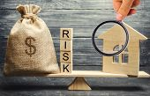 Money Bag, Blocks With The Word Risk And A Wooden House On The Scales. The Concept Of Losing Money W poster