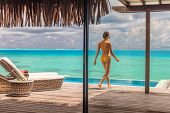 Luxury Bora Bora resort hotel woman walking on her private terrace deck of overwater bungalow villa  poster