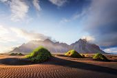 Gorgeous landscape with black sand desert dunes and grassy bumps near famous Stokksnes mountains on  poster