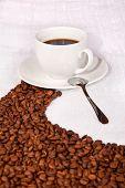 Постер, плакат: Кофейные бобы сделать путь к белым чашку кофе