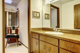 stock photo of outdated  - Simple browns and white bathroom in old outdated American house - JPG