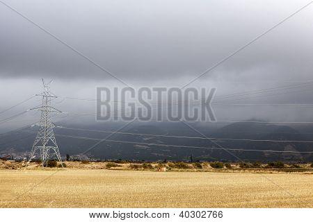 Electricity Pylon In A Field Of Straw