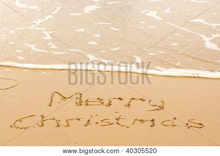 Merry Christmas Written In Sand On Beach