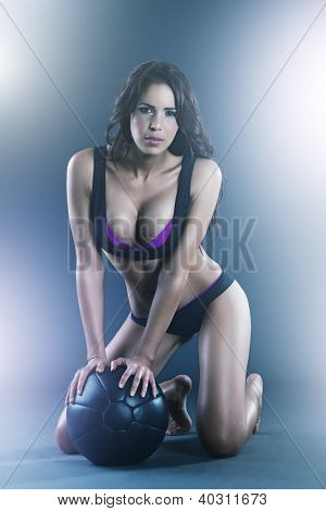 Sexy fitness instructor working out with a medicine ball