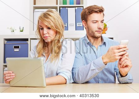 Couple looking at tablet computer and smartphone seperately in living room