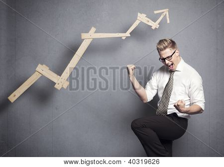 Concept: Winner in business. Thrilled young businessman cheering in front of positive business graph, isolated on grey background.