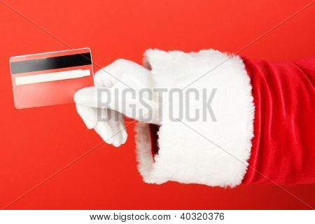 Santa Claus hand holding red credit card on red background