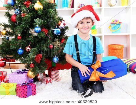 Little boy in Santa hat sits near Christmas tree with flippers