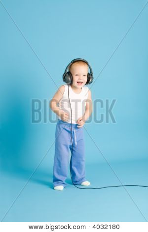 Joyful Boy Listening Music At Cord Headphones