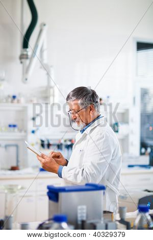 Senior doctor/scientist using his tablet computer at work (color toned image)