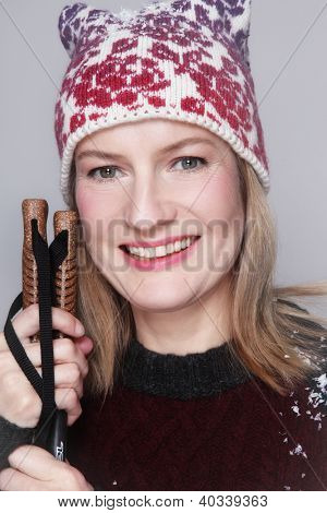 Beautiful happy smiling middle-aged woman in knitted hat and pullover with ski sticks in her hands