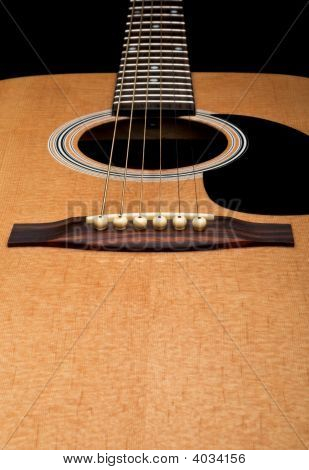 Close-Up Of Acoustic Guitar, Focus On The Bridge, On Black Background
