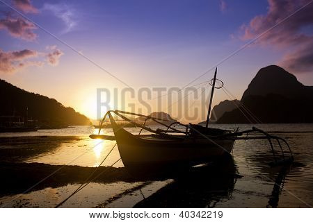 Boats moored at coastle sunset