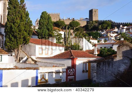 Medieval Houses In Ancient City Of Obidos, Portugal With Castle Walls  In Background