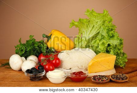 Ingredients for pizza on wooden table on brown background