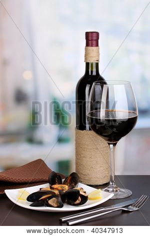 Snack of mussels with lemon and wine on plate on wooden table on room background