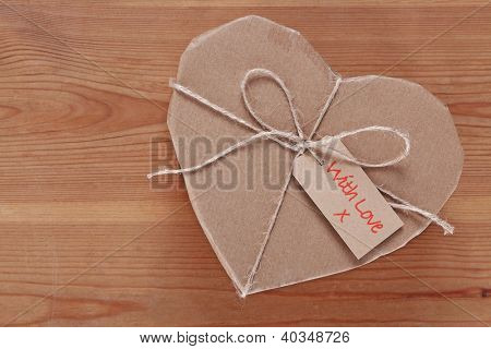 A heart shaped brown paper parcel with a label saying With Love.